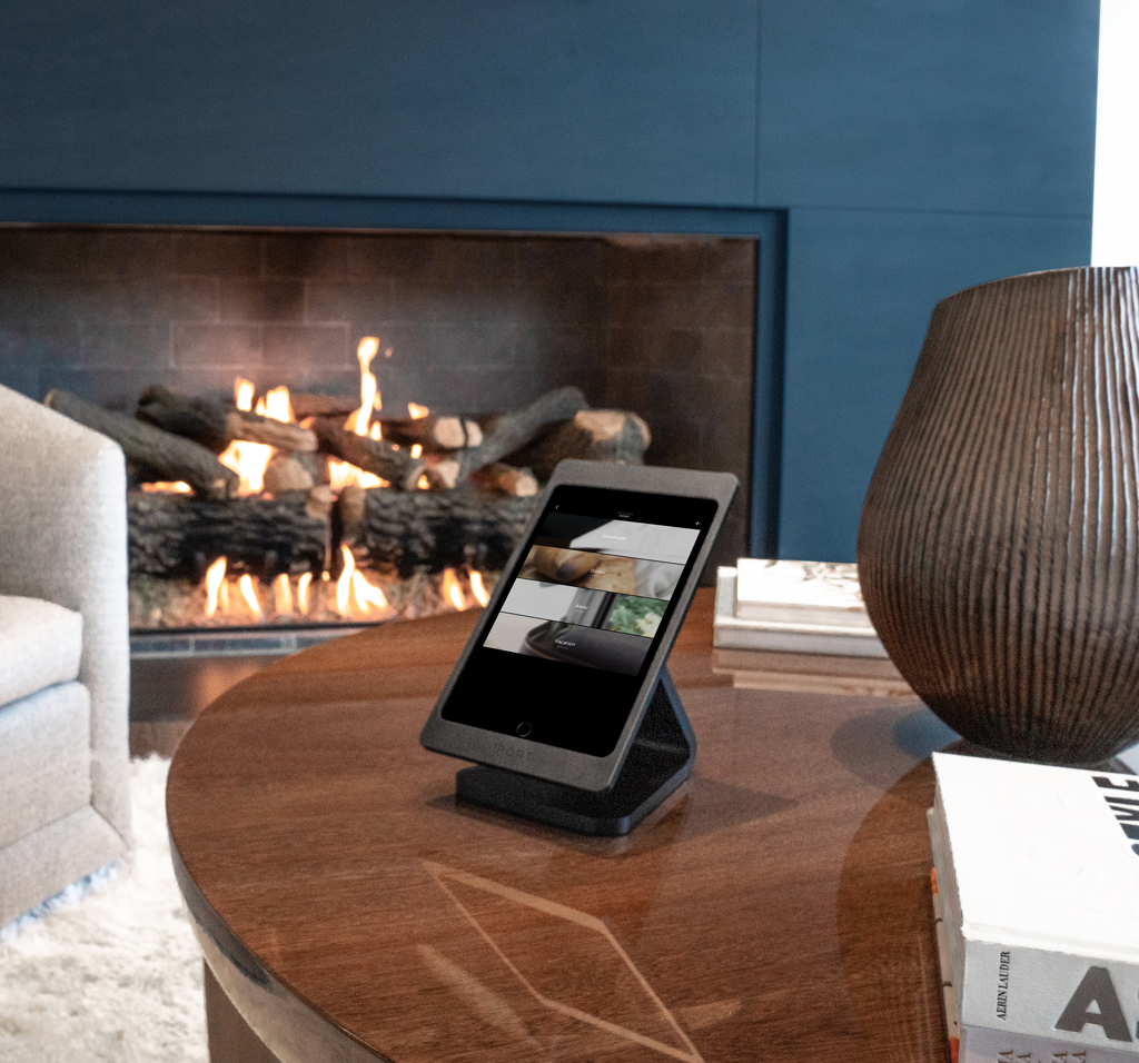Black IPORT LUXE, the wireless charging case and mount for iPad by IPORT, on a coffee table in a modern living room.