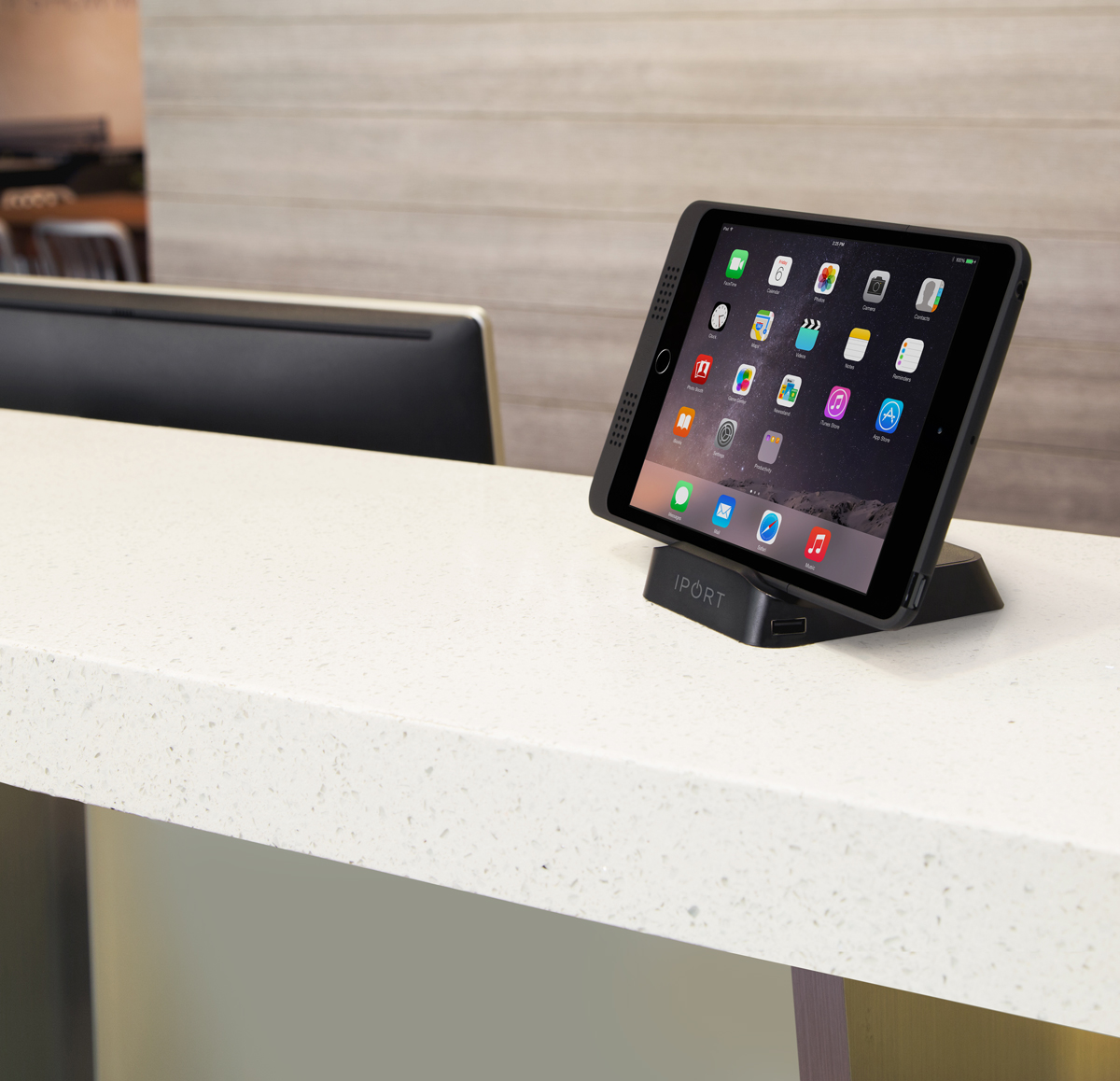 Black tablet docking station by IPORT on the front desk of a corporate office.