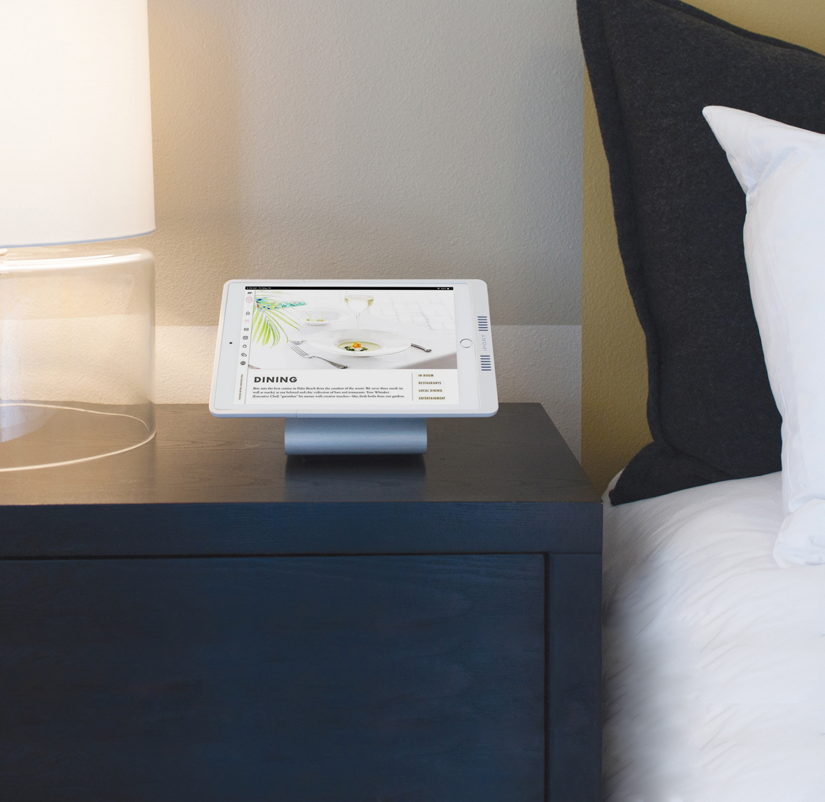 White iPad charging case with silver iPad charging station by IPORT on a bedside table in a hotel room.