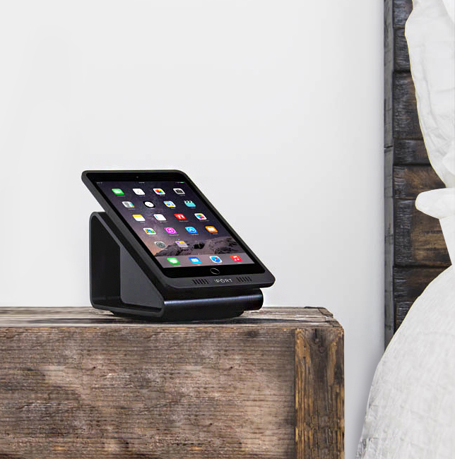 Black iPad wireless charging station by IPORT on a bedside table.
